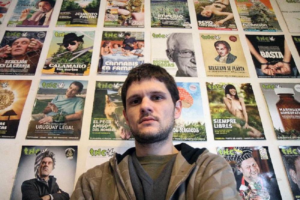 sebastian basalo, director de la revista thc, apoyado sobre una pared repleta de tapas de la revista